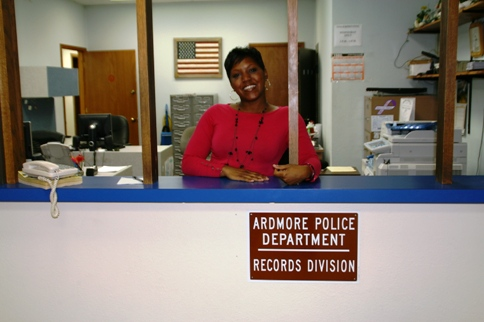 Records Clerk Melanie Taylor smiles from behind the counter at the Records Division Office
